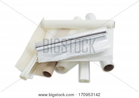 Several rolls of the plastic oven bags plastic food wrap aluminum foil and various parchment paper for household use on a light background.