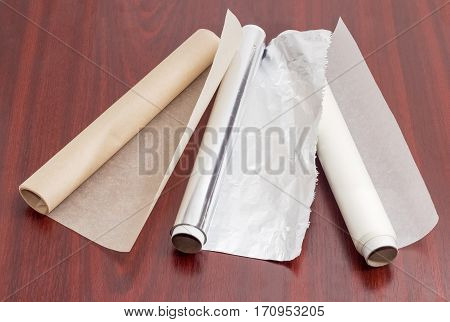 Two rolls of the various parchment paper and one roll of the aluminum foil for household use on a dark red wooden surface