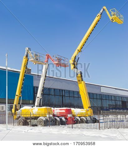 The three different self propelled wheeled hydraulic articulated boom lift with telescoping booms and baskets against the sky and the industrial building in winter sunny day