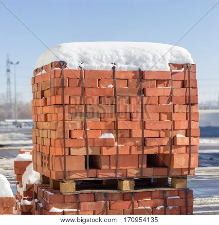 Wooden pallet of the red bricks covered snow on an another such pallet on a outdoor warehouse in winter sunny day