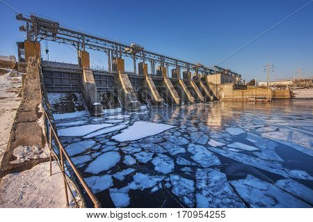 beautiful hydro electric station in winter against the blue sky