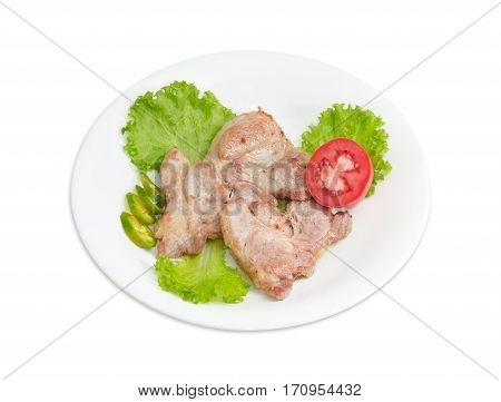 Several slices of fried pork neck on lettuce leaves sliced green chili and half of tomato on white dish on a light background