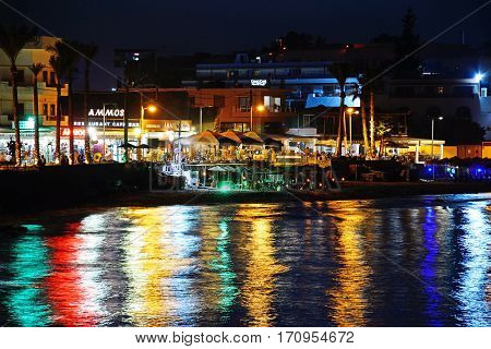 HERSONISSOS, CRETE - SEPTEMBER 18, 2016 - View of the beach and waterfront shops and restaurants at night Hersonissos Crete Greece Europe, September 18, 2016.