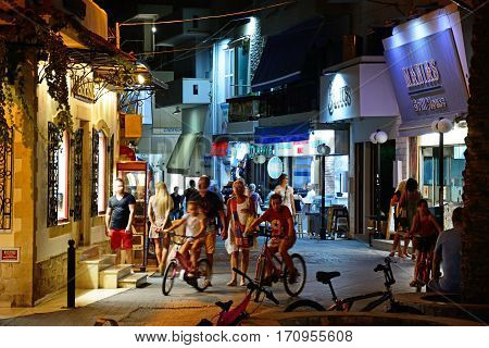 HERSONISSOS, CRETE - SEPTEMBER 18, 2016 - Tourists and locals enjoying the evening atmosphere in a harbour shopping street at night Hersonissos Crete Greece Europe, September 18, 2016.