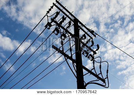 Electric pole connect to the high voltage electric wires with blue sky background.