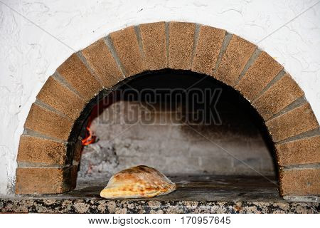 Freshly cooked Calzone in a wood fired oven Hersonissos Crete Greece Europe.
