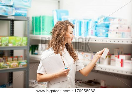 Pharmacist Woman In The Warehouse Looking At Boxes With Pills