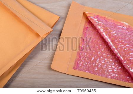 Open Used Yellow Blank Envelope With Transparent Bubble Wrap Or Packaging Shockproof On Wooden Table