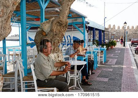 IERAPETRA, CRETE - SEPTEMBER 18, 2016 - Three elderly Cretan men sitting at a pavement cafe by the harbour Ierapetra Crete Greece Europe, September 18, 2016.