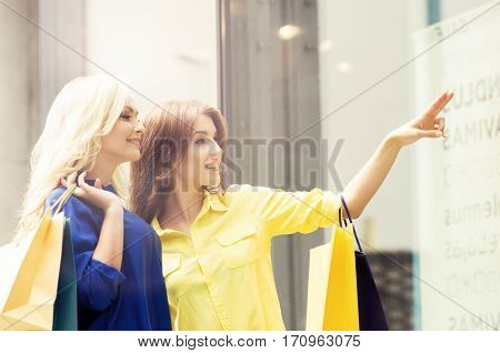 Pretty women with a shopping bags. Friends walking outdoor in a city. Discount, sale, shopping and money spending concept.