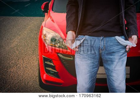 Man showing his empty pockets with red car parked on the street.