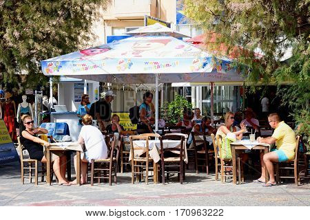 IERAPETRA, CRETE - SEPTEMBER 18, 2016 - Tourists relaxing at a pavement cafe Ierapetra Crete Greece Europe, September 18, 2016.