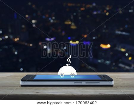 Restaurant cloche flat icon on modern smart phone screen on wooden table over blur colorful night light city tower Food delivery concept