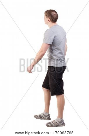 Back view of walking handsome man in shorts and sneakers.   Sports-dressed young man moves. going young guy. Rear view people collection.