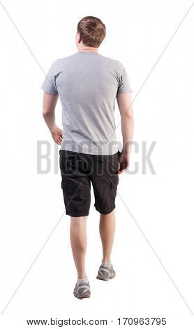 Back view of walking handsome man in shorts and sneakers.   Sports-dressed young man moves. going young guy. Rear view people collection.  backside view of person.