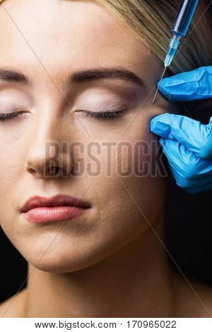 Woman receiving botox injection on her forehead in examination room