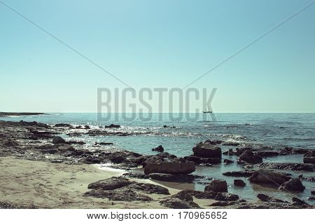 Uneven rocky shore of the Mediterranean Sea with a ship on the horizon sunny landscape
