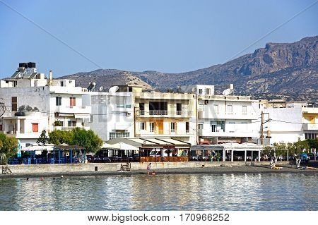IERAPETRA, CRETE - SEPTEMBER 18, 2016 - Tourists relaxing on the beach with town buildings to the rear Ierapetra Crete Greece Europe, September 18, 2016.