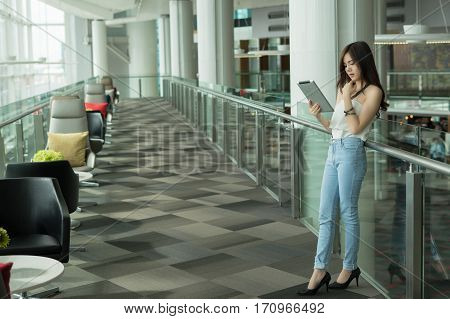 Beautiful Young Asian business women smiling and reading tablet standing at banisters and the stairs with happiness and concentrate .
