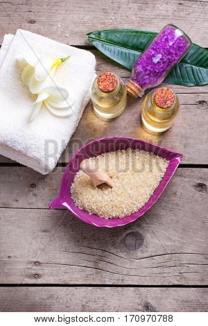Spa setting. Sea salt in bowl in form of leaf with towels and bottles with oil on vintage wooden background. Selective focus. Verical image.