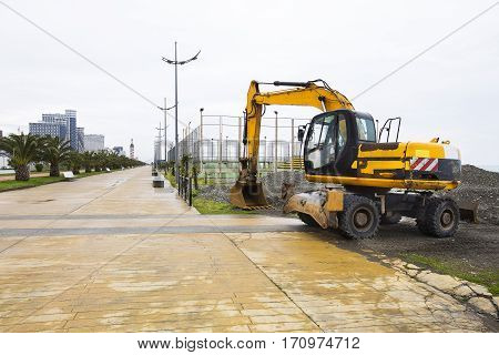 Excavator at a construction site. Yellow excavator in the background Sea
