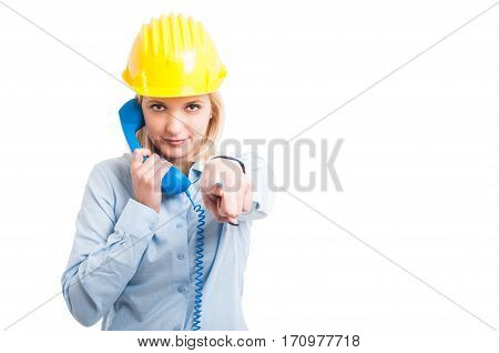 Female Architect Wearing Helmet Holding Telephone Receiver And Pointing