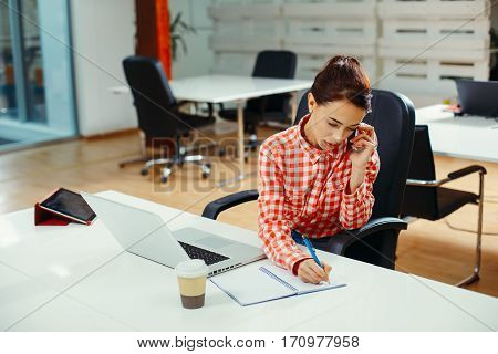 Secretary on phone writing a note in the office