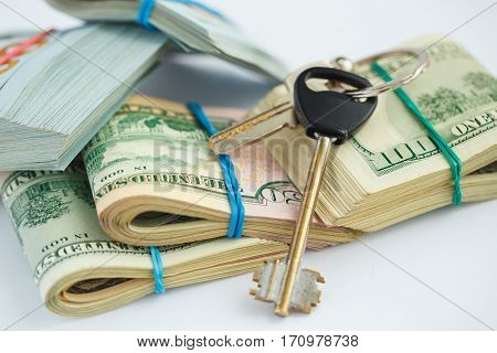 Success and got profit from business with pile of American dollars with keys - concept of buying new house
