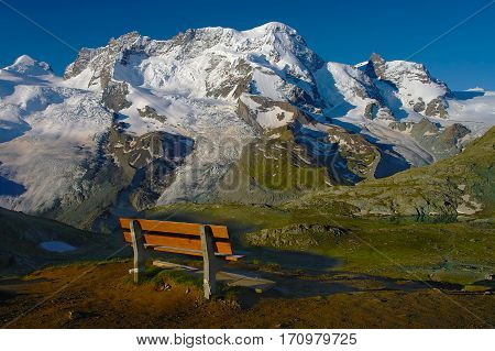 Scenic bench view over the snowy mountains Pennine Alps Switzerland