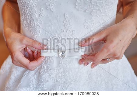 bride adjusts the belt on a white wedding dress in the morning