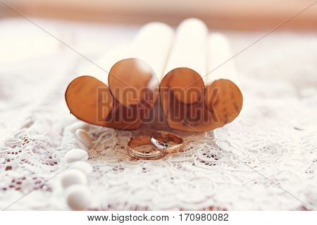gold wedding rings bride and groom on the background of hearts made of paper
