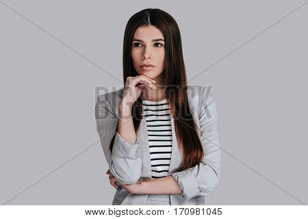 Thinking about solutions. Attractive young woman in smart casual wear holding hand on chin and looking away while standing against grey background