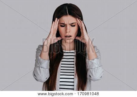 Feeling pain. Frustrated young woman in smart casual wear touching her head with hands and making face while standing against grey background