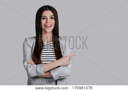 Pointing copy space. Beautiful young woman in smart casual wear keeping arms crossed and looking at camera with smile while standing against grey background