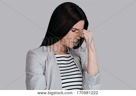 Feeling so tired. Frustrated young woman in smart casual wear massaging nose and keeping eyes closed while standing against grey background