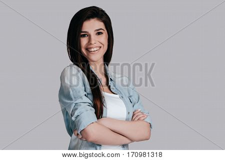 Young and beautiful. Gorgeous young woman in jeans wear keeping arms crossed and looking at camera with smile while standing against grey background