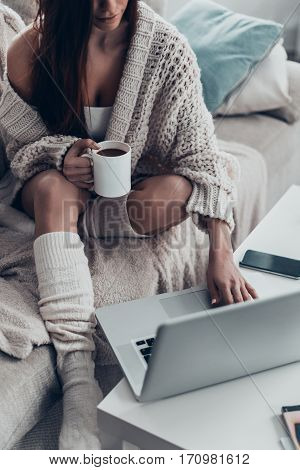 Surfing the net at home. Gorgeous young woman holding cup and using computer while sitting on couch at home