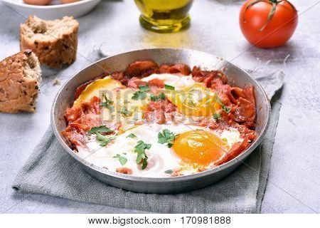 Fried eggs with tomato and bacon in frying pan