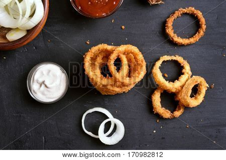 Fried onion rings with sauce on black background top view