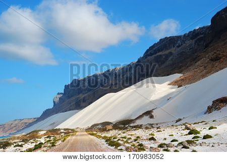 Dirt road along Indian ocean coast between ocean and mountains with huge white sand dunes on the Socotra island, Yemen
