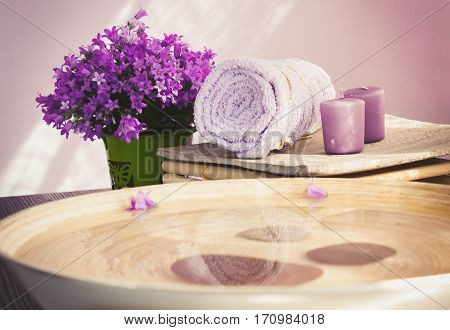 Natural wellness and spa setting with flowers and towel and water for treatment. Dayspa cosmetics products