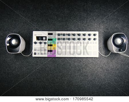 Synthesizer with white speakers connected to it