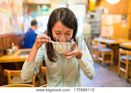 Woman eating soup in japanese restaurant