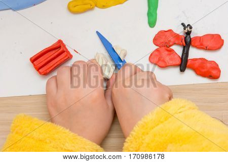 The Child Cuts Off A Piece Of Plasticine Stack, Close-up