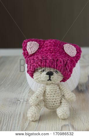 Knitted crochet small pink hat on the sad bear. Women's hat for feminists march protest. Creative craft work