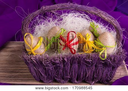 Easter Egg Decorative In Twine In Purple Basket On Wooden Table On Purple Background.