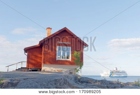 GRISSLEHAMN SWEDEN - JUL 12 2016: Red cottage used by swedish artist Albert Engstoem passenger ferry and blue sea in the swedish archipelago in the background. July 12 2016 Grisslehamn Sweden