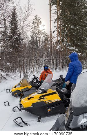 Men and a woman stopped at a clearing while traveling in the winter woods on snowmobiles.