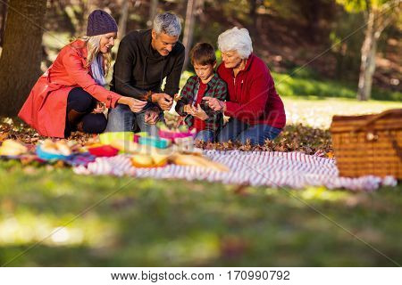 Multi-generation family holding autumn leaves at park