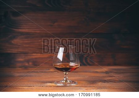 Glass Of Brandy Or Cognac On The Wooden Table.